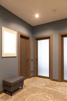 ブラウンとグレーを基調としたニュートラルな色合いのモダンな玄関廊下。