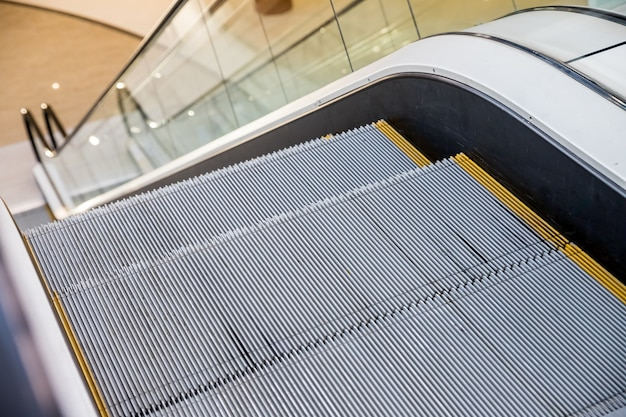 현대 에스컬레이터 회색 금속 질감 단계 검은 난간 투명 아크릴 또는 플라스틱 측면 에스컬레이터 쇼핑 센터 또는 사무실 건물 또는 지하철 역