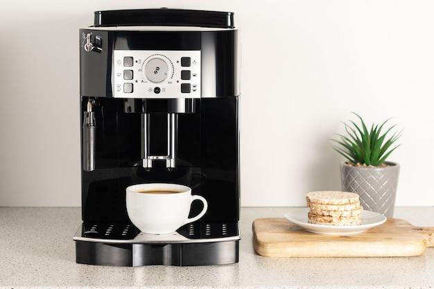 Современная кофемашина эспрессо с чашкой в интерьере крупного плана кухни.