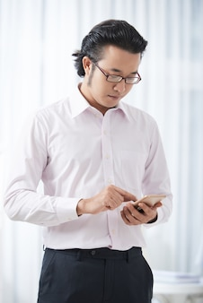 Modern ethnic businessman using smartphone