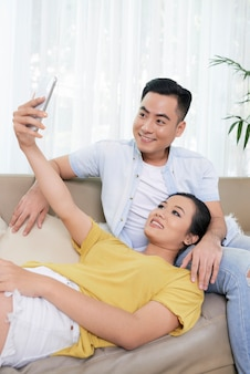 Modern ethnic couple taking selfie on couch