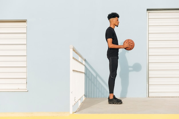 Modern ethnic man with basketball on street