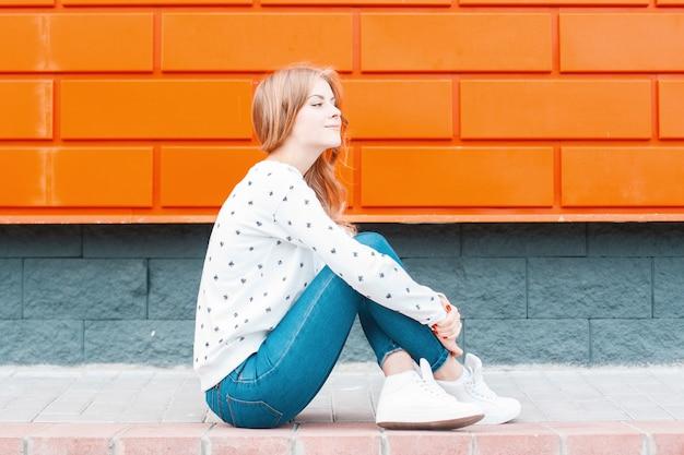 스웨터에 운동화 빈티지 청바지에 현대 유럽 세련 된 젊은 여자는 오렌지 벽 근처 보도에 앉아