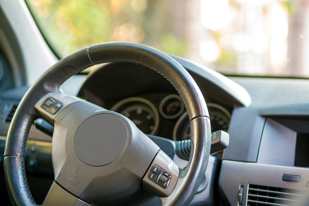 Modern expensive car black luxurious interior. steering wheel, dashboard, windshield and mirror. transportation, design, modern technology concept.