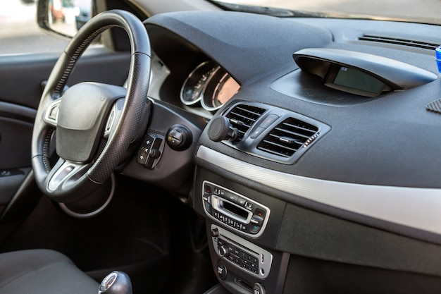 Современный дорогой автомобильный салон. приборная панель и руль черного цвета. транспорт, дизайн, концепция современных технологий.