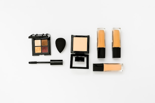 Modern eye shadow palette; blender; mascara brush; foundation bottles and compact powder on white backdrop