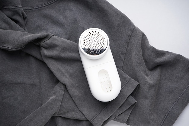 Modern fabric shaver and clothes on color background, flat lay.