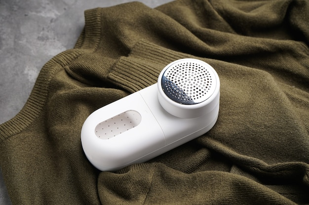Modern fabric shaver and clothes on grey background.