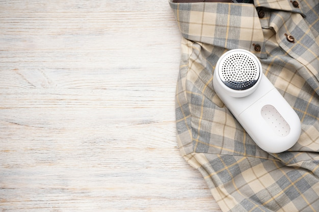 Modern fabric shaver and clothes on wooden background, space for text. top view.