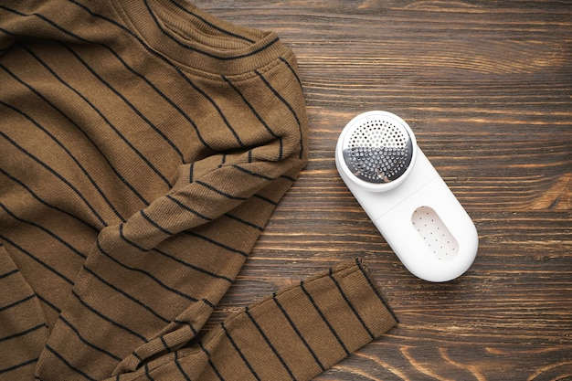 Modern fabric shaver and clothes on wooden background. top view.