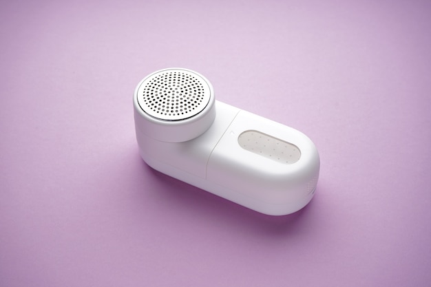 Modern fabric shaver on color background. close-up.