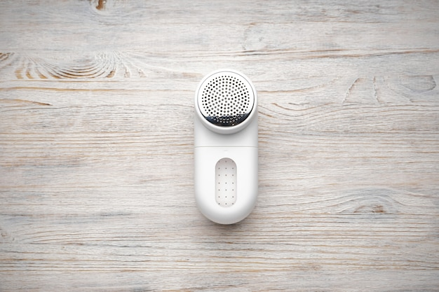 Modern fabric shaver on a wooden background, top view.