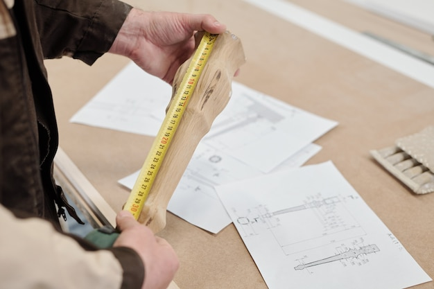 Modern factory worker measuring wooden part of furniture while holding it over sketches on table and comparing length indication