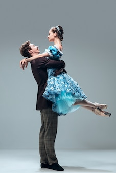 현대 페어리 테일. 회색 스튜디오 배경에 고립 된 아름 다운 현대 볼룸 댄서. 왈츠, 탱고, 슬로우 폭스, 퀵 스텝을 춤추는 감각적 인 프로페셔널 아티스트. 유연하고 무중력.