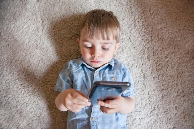 私たちの日常生活における現代の家族のライフスタイルとテクノロジー。子供の電子機器のペアレンタルコントロール。