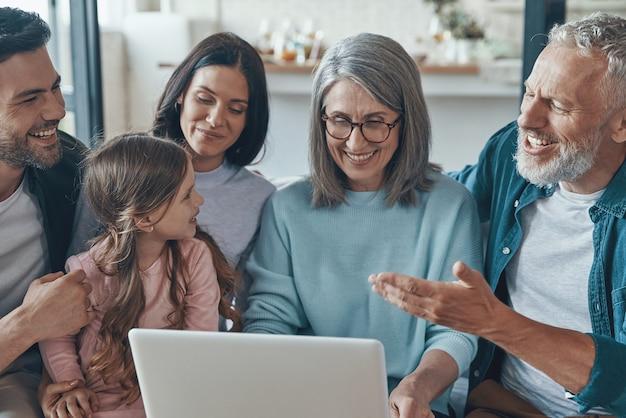Современная семья проводит время вместе и улыбается, сидя на диване у себя дома