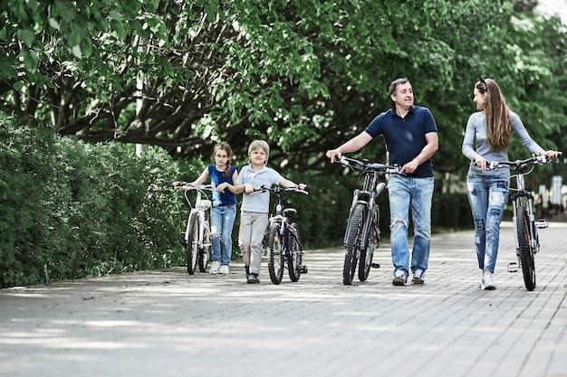 自転車を持った現代の家族が都市公園を歩きます。健康的なライフスタイルの概念
