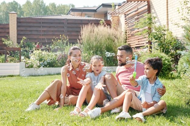 裏庭で夏の日を過ごす2人の子供、小さな男の子がシャボン玉を作る現代の家族
