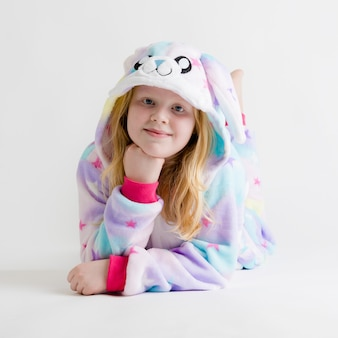 Modern fashion - beautiful blonde girl posing on white in kigurumi pajamas, bunny costume