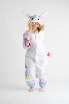 Modern fashion - красивая блондинка позирует на белом фоне в пижаме кигуруми, в костюме зайчика