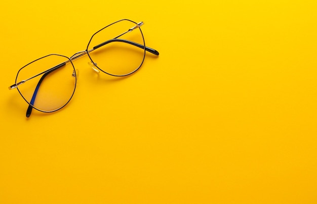 Modern fashionable eye glasses on yellow background.