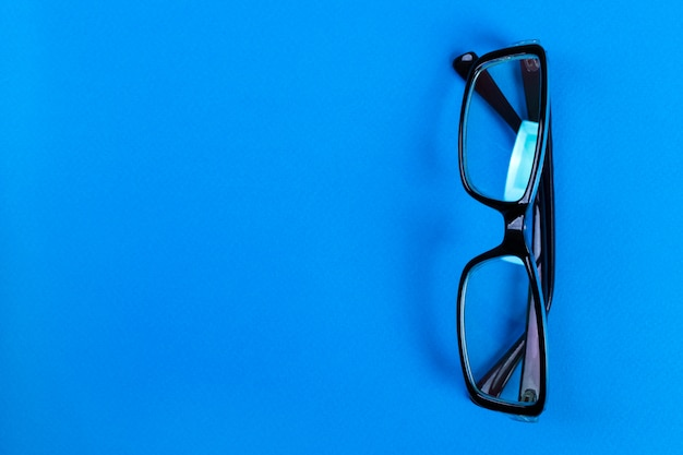 Modern fashionable and office spectacles on blue background