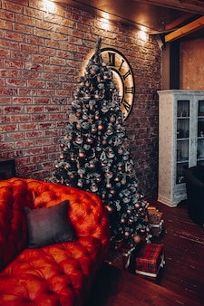 Modern fashionable red leather couch with cushions. cropped christmas tree. brick wall. loft design.