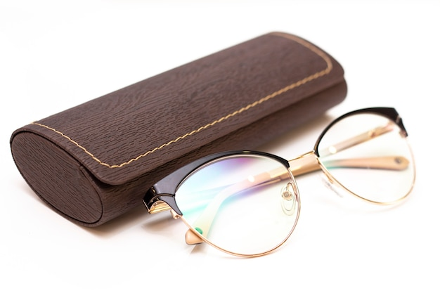 Modern fashionable womens gold glasses for sight and a leather case on a light background.