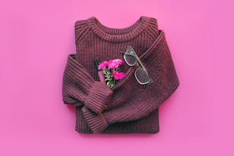 Modern female minimal background with cozy burgundy sweater, jeans, flowers, lip gloss