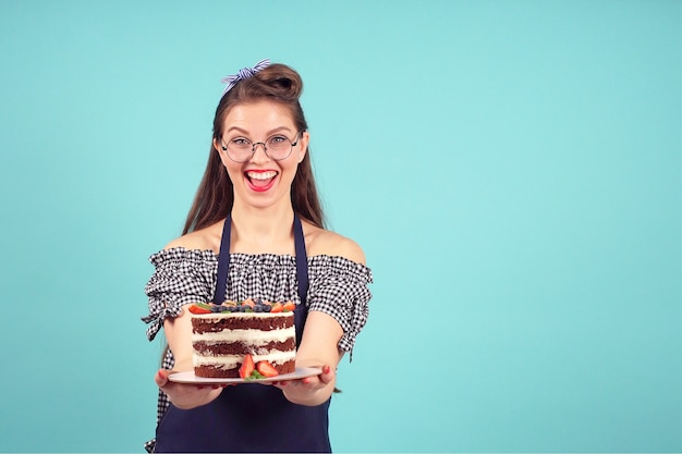 Modern female pastry chef smiles at the camera with a cake in her hands on a blue background