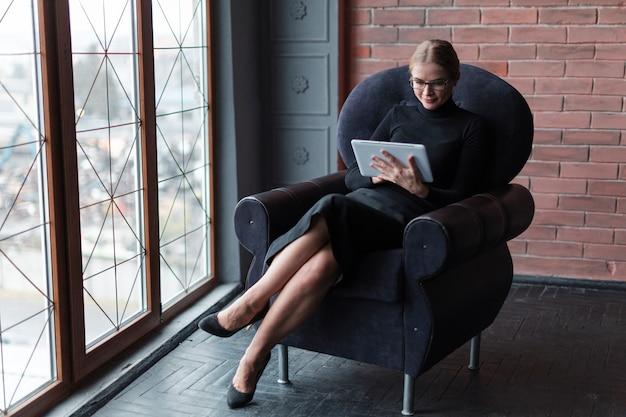 ソファの上にタブレットで現代の女性