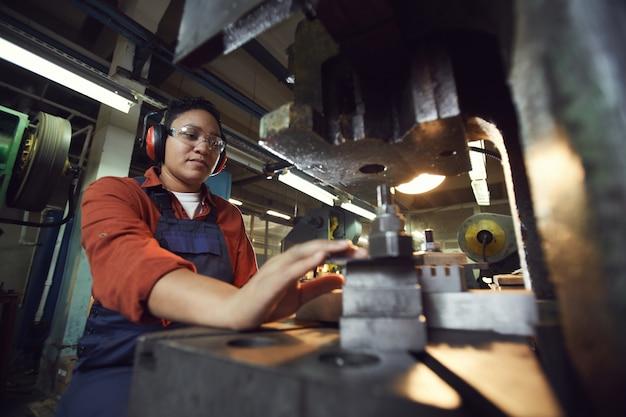 Modern female worker using heavy machinery