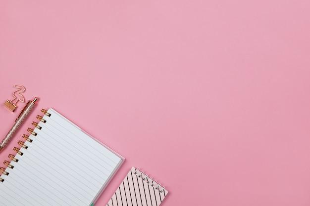 現代の女性作業スペース、トップビュー。ノートブック、ペン、ピンクの背景のクランプ、コピースペース、フラットレイ。フリーランサー、学生のデスクトップ。自宅から仕事、学校、教育概念に戻る。横