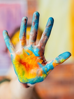 Modern fine art performance. closeup of hand dirty with blue and yellow paint