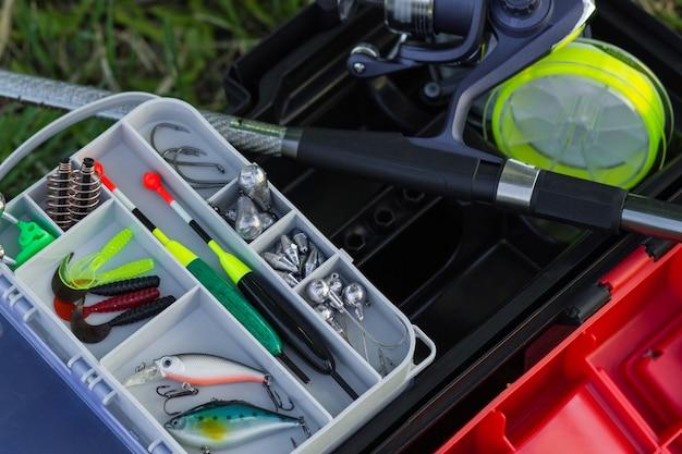 ボックス内の釣りリール釣り竿釣りフロートラインとウェイトのモダンな釣り道具の上面図