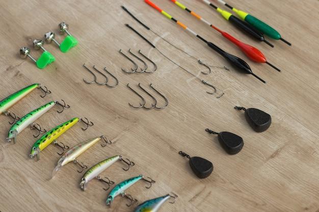 現代の釣り道具-美しい木製の背景に浮き、ルアー、ウェイト、ベルを釣ります