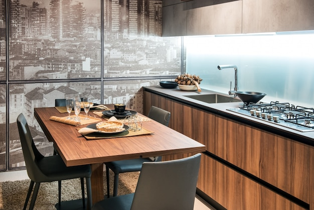 Modern fitted kitchen with table and glass wall
