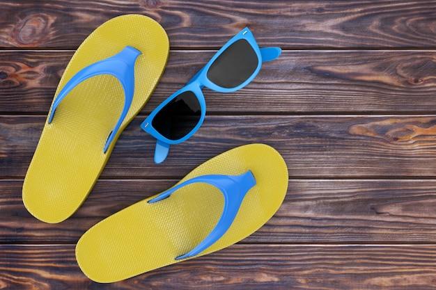 木の床に青いサングラスをかけたモダンなビーチサンダル。 3dレンダリング