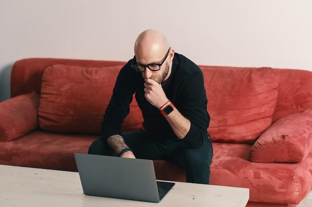 현대적인 인테리어에 노트북에서 작업하는 수염과 안경을 가진 현대 집중된 남자