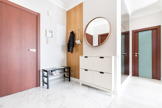 Modern, fresh white hallway interior. entrance door, wooden hanger with hanging clothes and a lady's purse. there are shoe cabinet near the door, and round mirror on the wall