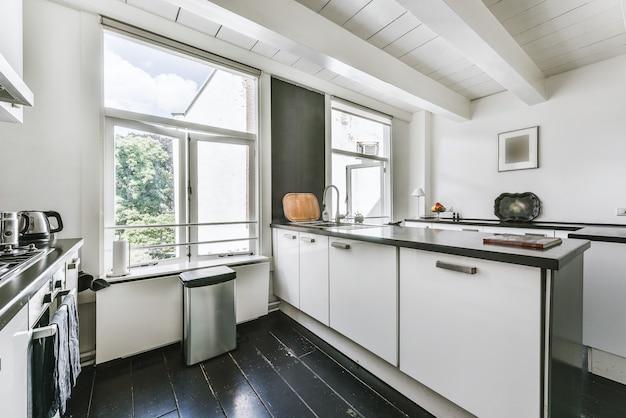 白い梁のある天井と大きな窓のある家の中に黒い床と白いキャビネットを備えたモダンな家具付きキッチン