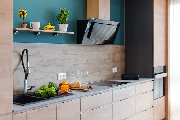 豪華なキッチンのモダンな家具。木製の家具、ランプ、コンクリート要素、植物を備えたロフトアパートメントのミニマリストスカンジナビアのインテリア。
