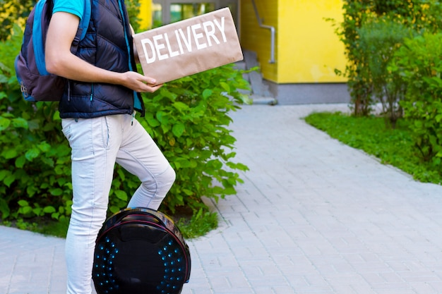 Modern future delivery. man male guy in delivery uniform and delivery box with electric transport / eco ecology electric unicycle / self balancing wheel delivers ordered package to receiver Premium Photo