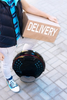Modern future delivery. man male guy in delivery uniform and delivery box with electric transport / eco ecology electric unicycle / self balancing wheel delivers ordered package to receiver