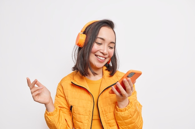 Modern gadget and lifestyle concept. positive asian woman concentrated into smartphone display enjoys listening music from playlist wears orange jacket smiles cheerfully isolated over white wall
