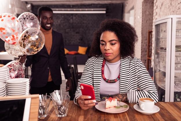 Современный гаджет. милая позитивная женщина смотрит на экран своего смартфона, сидя перед куском торта