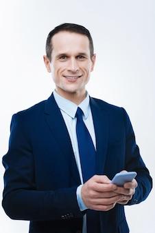 モダンなガジェット。彼のスマートフォンを保持し、それを使用しながらあなたを見ているスマートインテリジェントな素敵なビジネスマン