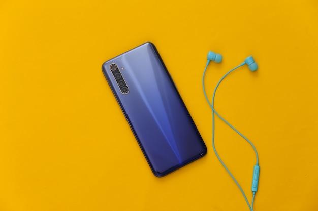 현대 가제트. 노란색에 파란색 이어폰과 현대 스마트 폰