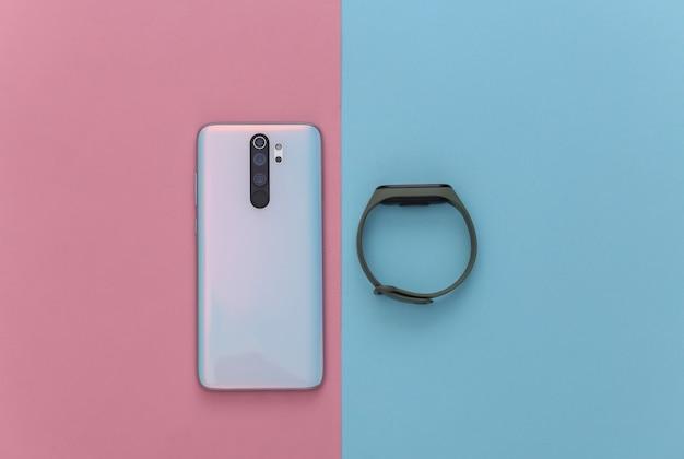 現代のガジェット。青ピンクのパステルカラーのスマートフォンとフィットネススマートブレスレット