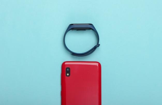 現代のガジェット。ブルーパステルカラーのスマートフォンとスマートブレスレット